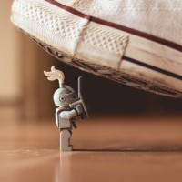Gray mini figure under white sneaker, por James Pond (via Unsplash)
